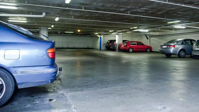 Blick in eine Tiefgarage (Symbolbild): Im Vordergrund ein Auto, hinten mehrere Fahrzeuge und einige leere Parkfelder, Sichtbeton-Bau.