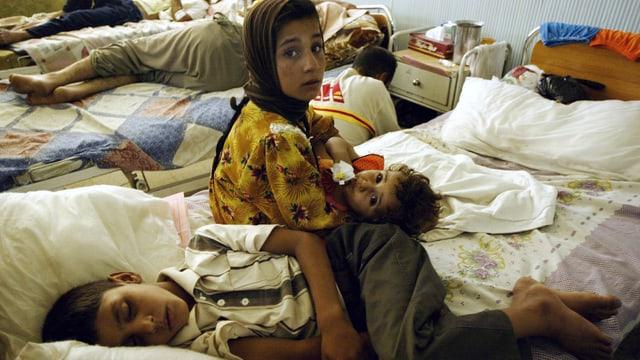 Irakische Mutter sitzt neben ihrem verletzten Kind auf einem Spitalbett