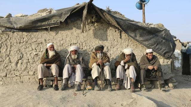 Afghanische Männer vor einer Lehmhütte