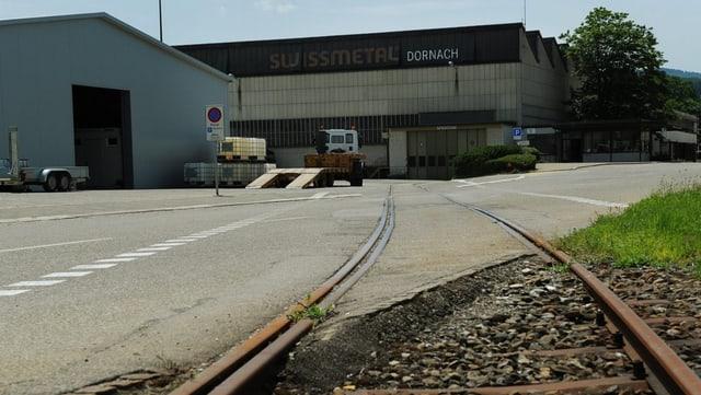 Blick auf zwei Fabrikgebäude der Swissmetal, im Vordergrund eine Strasse und ein Güterbahn-Gleis.
