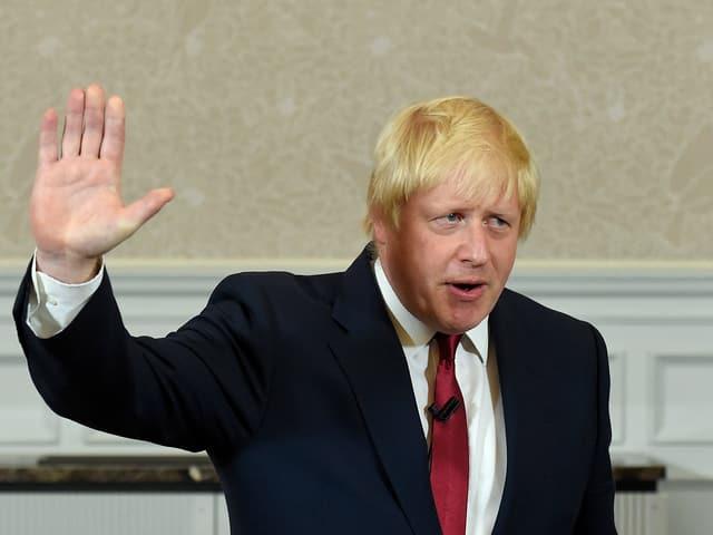 Boris Johnson hält rechte Hand hoch