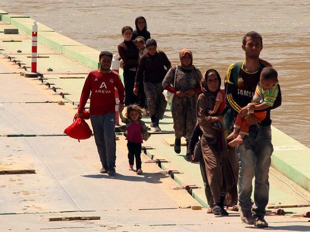 Männer und Frauen mit Kindern ohne Gepäck schreiten über eine Brücke.