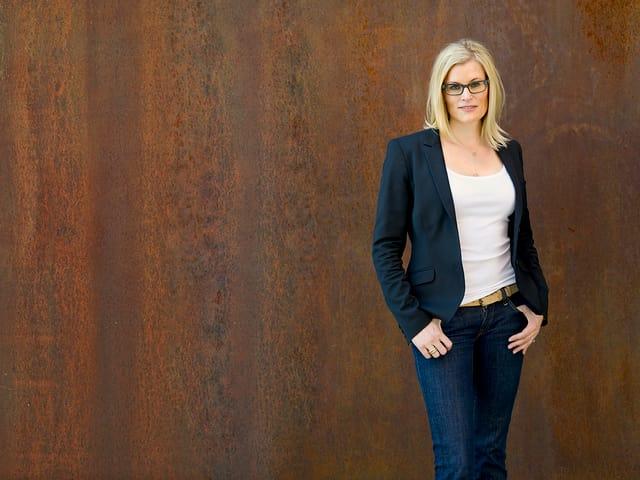 Eine blonde Frau mit langen Haaren vor rostbraunem Hintergrund.