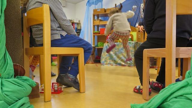 Kind springt über den Gummitwist, rundherum sitzen die anderen Kindergärtner