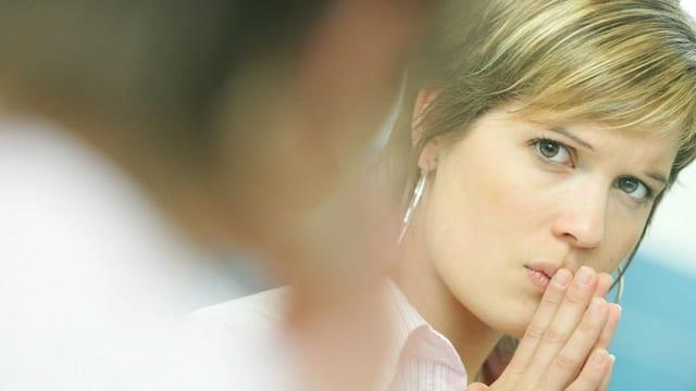 Eine Frau blickt traurig zu ihrem Chef