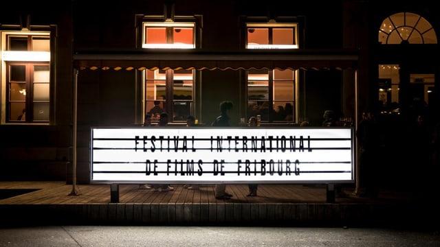 Eine Leuchtreklame als Ankündigung des Festivals steht vor einem Kino.