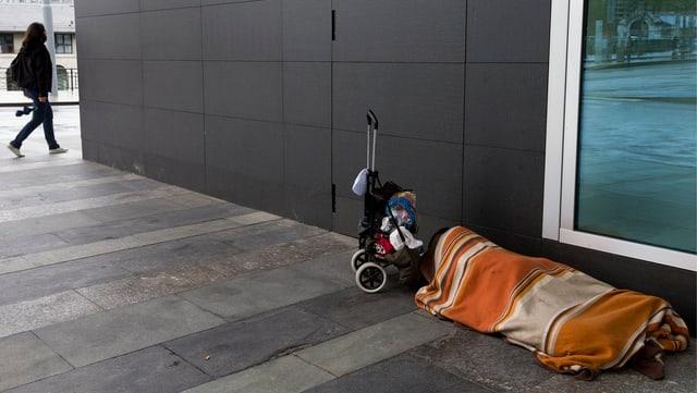Ein Obdachloser liegt eingewickelt in eine Decke auf einem Trottoir in Genf.