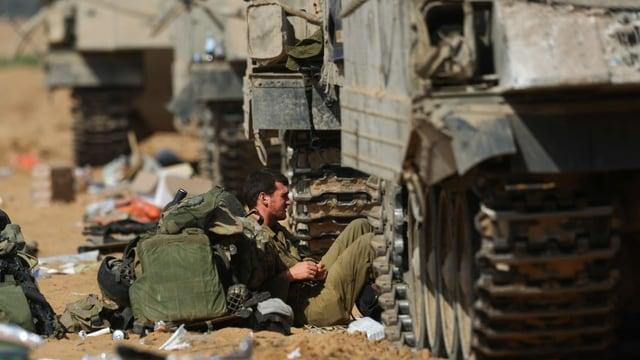 Soldat sitzt neben Militärfahrzeugen am Boden und ruht sich aus.