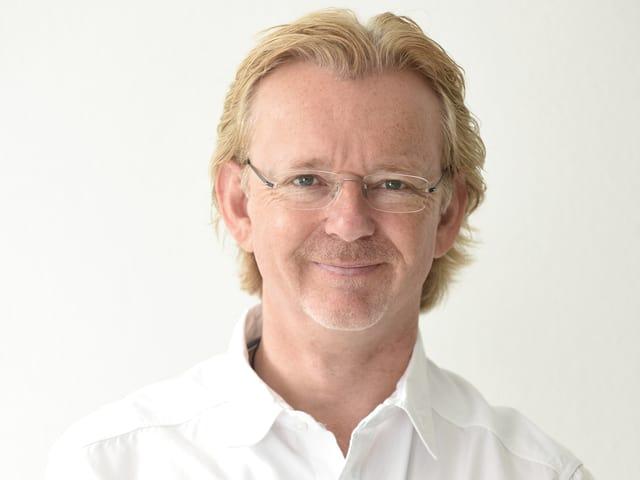 Der blondhaarige Moderator trägt eine Brille und ein weisses Hemd.