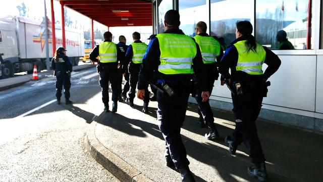 Polizeibeamte in Genf, von hinten, wie sie aus dem Bild marschieren.
