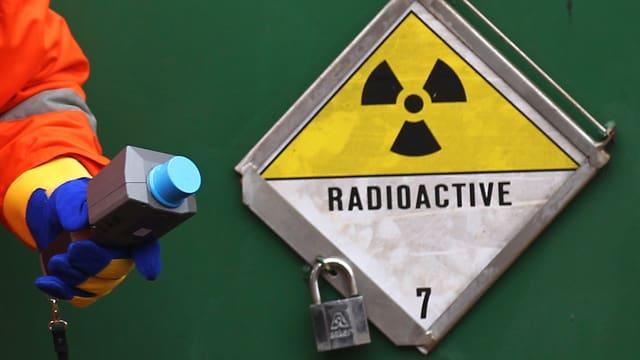 Gelb-weisses Warnschild vor Radioaktivität auf grüber Wand. Links ein Arm in Sicherheitskleidung.
