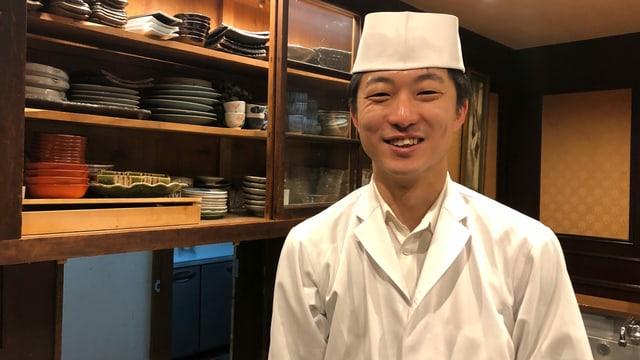 Amano in weisser Kochtracht und Mütze.