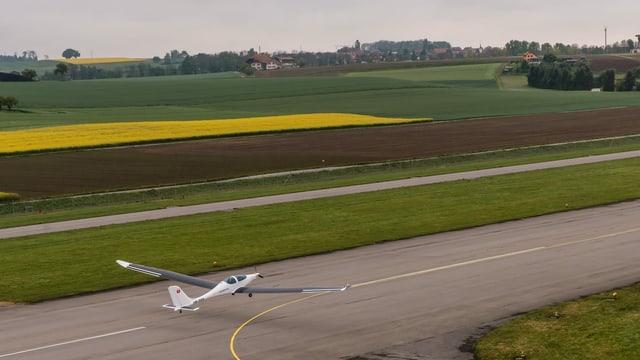 Ein Flugzeug mit Solarpanels auf den Flügeln beim Start auf einem ländlichen Schweizer Flughafen.