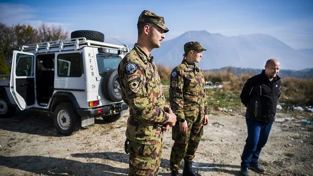 Zwei Swisscoy-Soldaten in Tarntenue stehen neben einem Zivilisten, dahinter ein weisses Fahrzeug, angeschrieben mit KFOR.