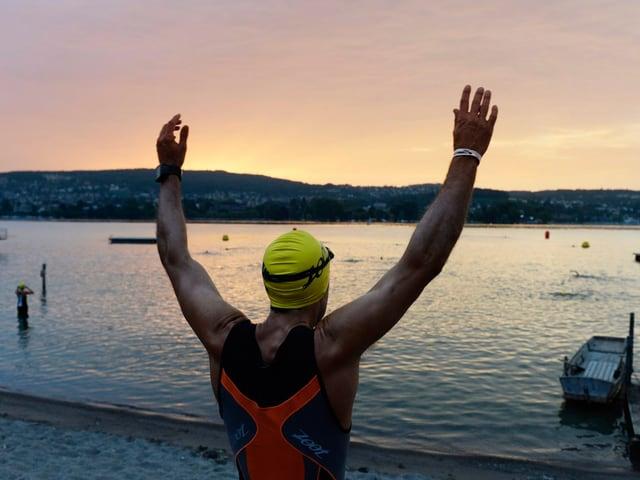 Zu sehen ist eine Schwimmer am Zürichsee im Morgengrauen.