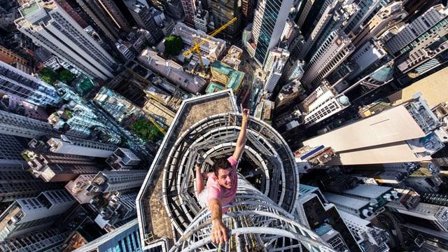 Mann hängt mit einem Arm an einer Leiter über den Hochhäusern einer Grossstadt.
