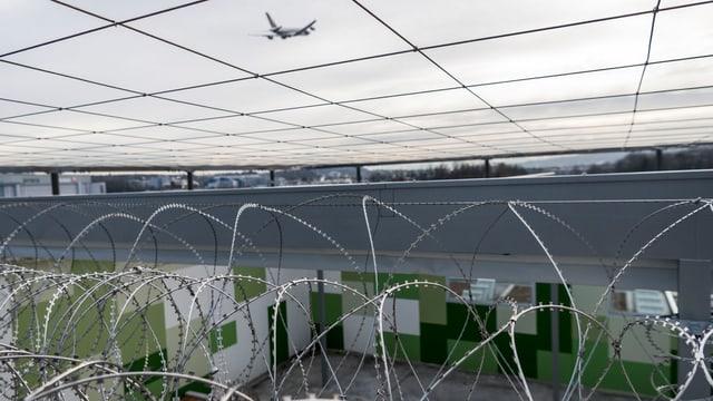 Stacheldraht im Flughafengefängnis von Zürich-Kloten – darüber ist ein Flugzeug am Himmel zu sehen