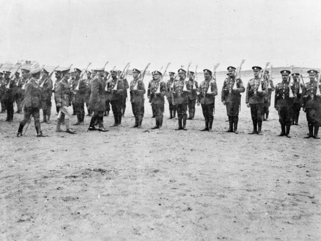 Altes Bild in Schwarz-Weiss: Soldaten stehen aufgereiht in der Wüste,