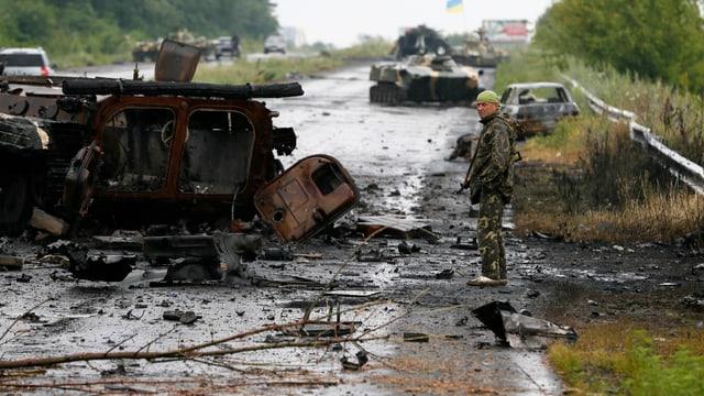 Ein ukrainischer Soldat steht neben einem zertörten Panzer