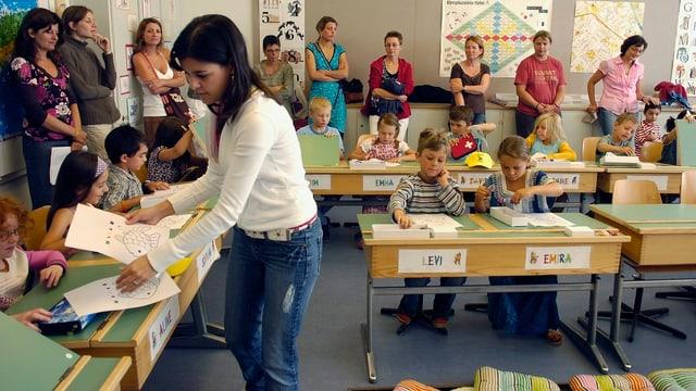 Eine Schulklasse mit Lehrerin, im Hintergrund die Mütter der Schüler.