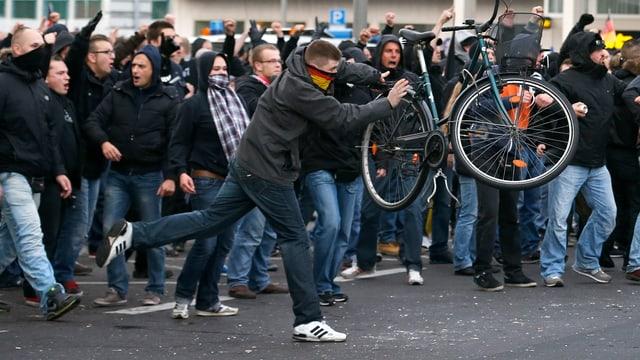 Protestierende Hooligans in Köln. Im Vordergrund wirft einer ein Velo.