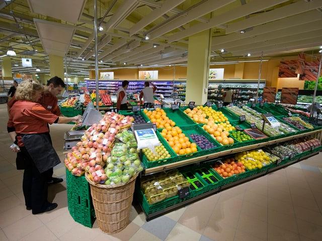 Migros Mitarbeitende füllen das Gemüseregal