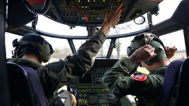 Dus pilots da l'armada svizra en il helicopter.