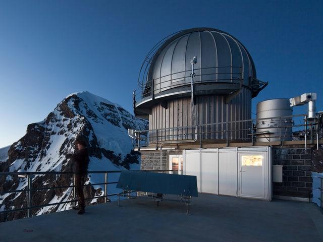 Ein Wissenschaftler steht vor der Forschungsstation am Jungfraujoch und macht ein Foto vom Nebel über dem Lauterbrunnental.