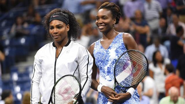 Serena und Venus Williams lächeln am Netz in die Kameras.