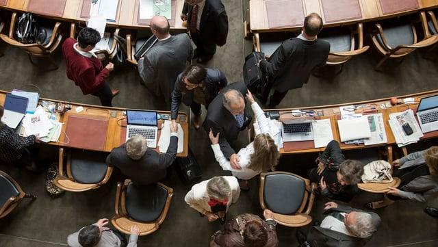 Blick von oben auf Personen, die um Tische stehen.
