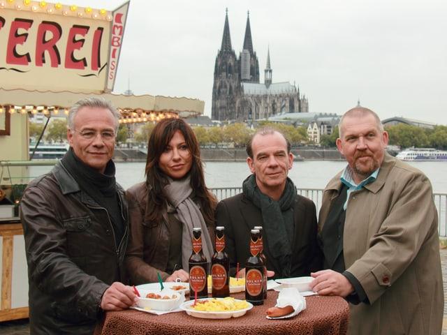 Drei Männer und eine Frau bei einem Imbissstand mit Wurst und Bier.