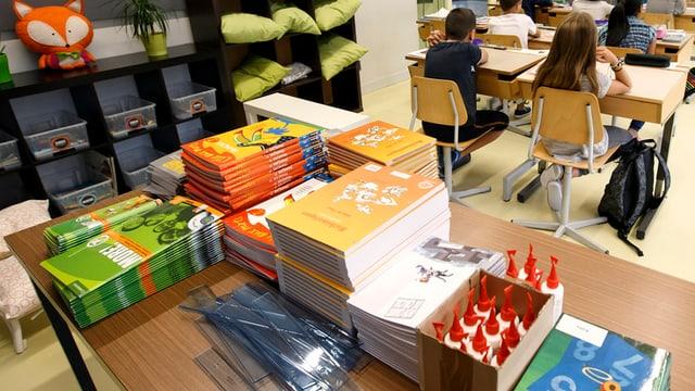 Ein Tisch in einem Schulzimmer mit vielen Büchern