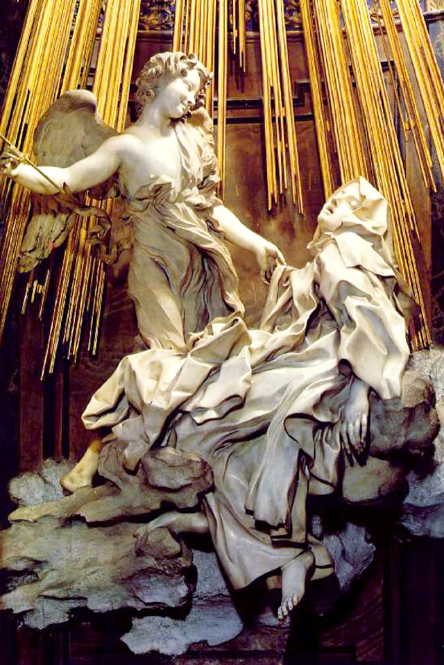 Eine Marmorstatue steht unter goldenen Strahlen: Sie zeigt eine Frau in wallenden Gewändern, junger Engel mit Pfeil zielt auf sie.