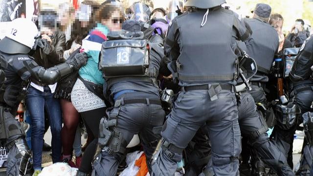 Polizeibeamte stellen sich gegen Demonstrantinnen.