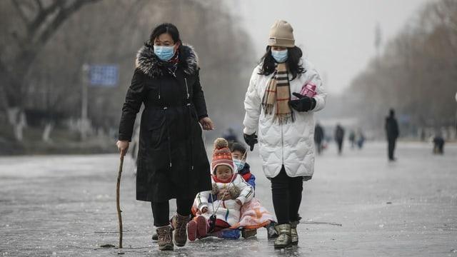 Zwei Frauen ziehen Kinder auf Schlitten in Schanghai