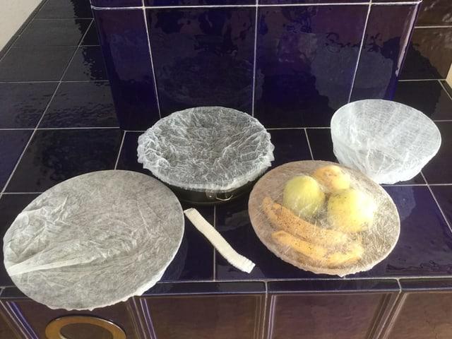 Schalen und Teller mit Haarnetzen zugedeckt.