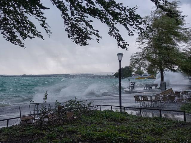 Uferpromenade mit aufgepeitschtem See, Gischt weht an Land und überall liegen umgestürzte Stühle.