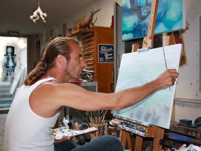 Ein Mann sitzt vor einer Leinwand und malt ein Bild.