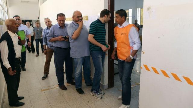 Männer in einer Reihe vor dem Raum wo sie ihre Stimmen abgeben können.