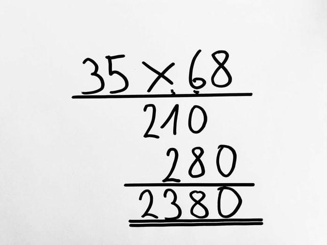 Auf einem Blatt steht die schriftliche Multiplikation von 35 x 68