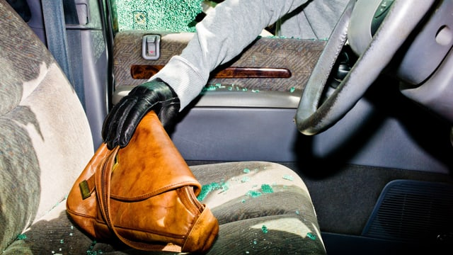 Ein Dieb greift durch ein kaputtes Autofenster nach einer Handtasche