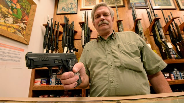 Ein Mann hält eine Pistole in die Kamera. Er verkauft Waffen in einem Geschäft.