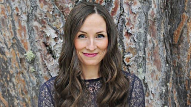 Porträt von Julie Fowlis vor einem Baumstamm.