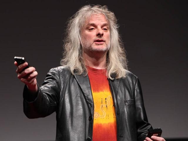 Portrait von David Chalmers mit iPhone in der Hand.