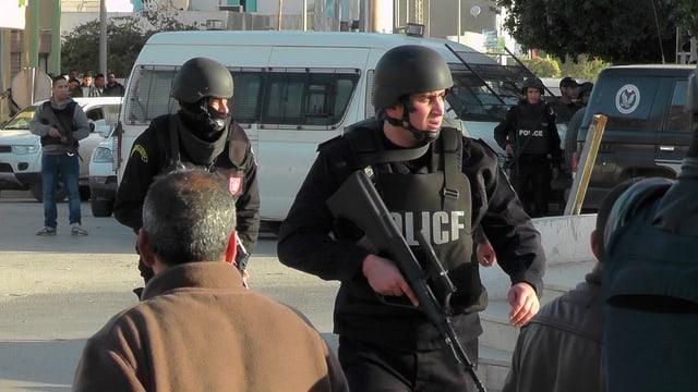 Schwerbewaffnete Polizisten mit Stahlhelm und kugelsicherern Westen, auch Passanten stehen herum.