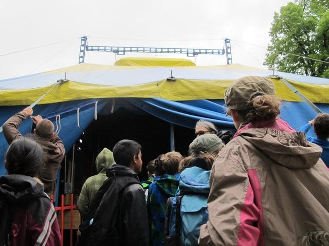 Das Publikum steht am Eingang zu einem Zirkuszelt.