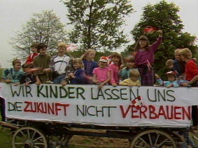 """Kinder auf einem landwirtschaftlichen Wagen mit dem Transparent """"Wir Kinder lassen uns die Zukunft nicht verbauen""""."""