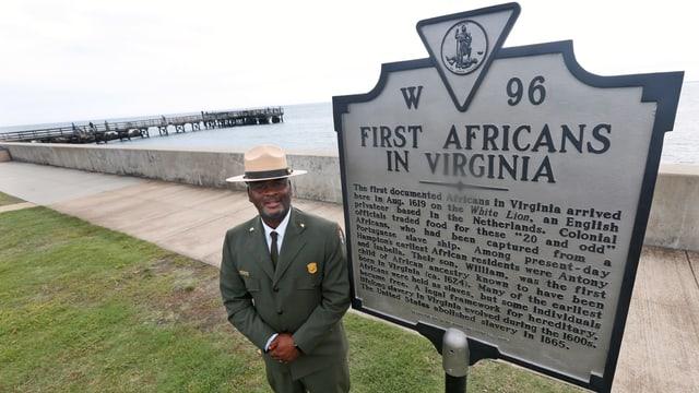 Mann steht vor Tafel. Darauf steht: First Africans in Virginia.
