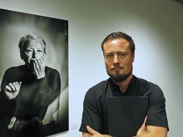 Ein Mann steht vor einem Porträt.