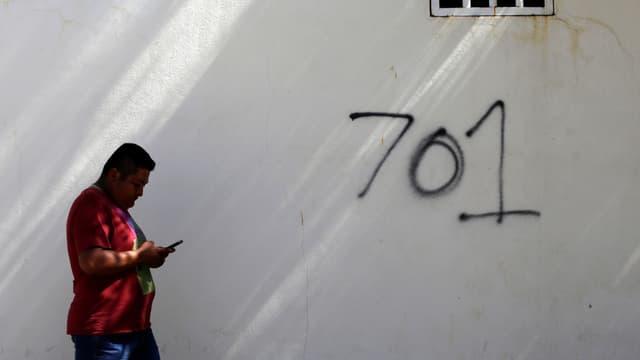 Symbolbild mit einem Mann am rechten Bildrand in roter Jacke, der an einer weissen Mauer mit der Aufschrift «701» vorbeigeht. 701 - das war Guzmáns Platz auf der Liste der reichsten Menschen des US-Magazins «Forbes».